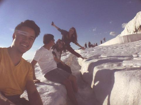 Image of author and friends sitting by a trench dug in snow.