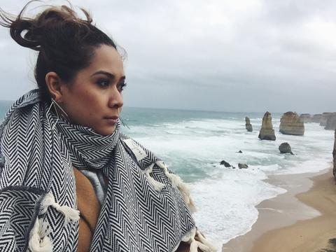 Image of the author gazing at the beauty of the 12 Apostles amidst the gloomy and windy weather.