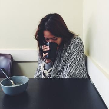 Image of the author enjoying a cup of coffee while snuggling under her Lagoona peshtemal shawl.