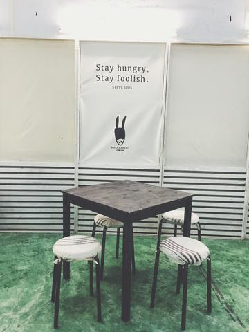 "Image of an empty table with 4 stools with poster in the background says ""Stay Hungry, Stay Foolish"""