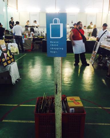 Image of crates of recycled bags under a pole with attached poster promoting their use.